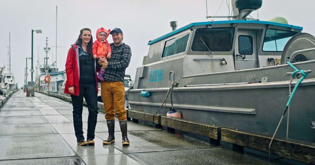 fishing family stands on dock next to boat